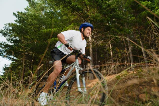 Человек на горном велосипеде по грунтовой дороге — стоковое фото