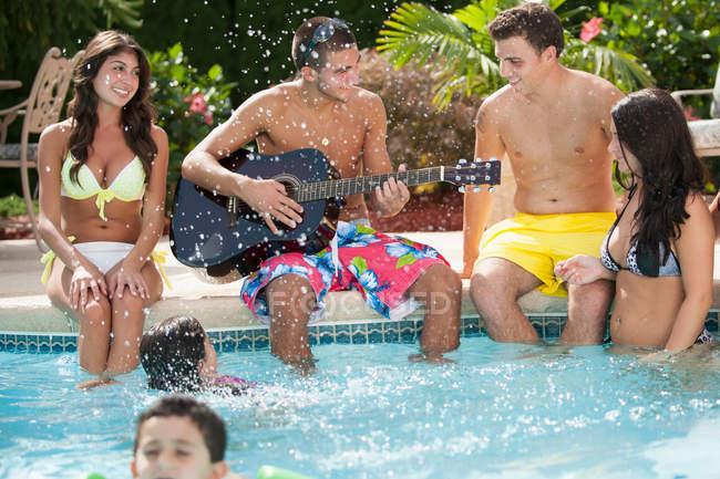 Las personas felices relajándose junto a la piscina, enfoque selectivo. - foto de stock