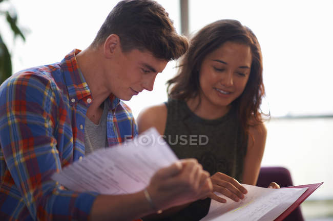 Young female and male college students reading file in common room — Stock Photo