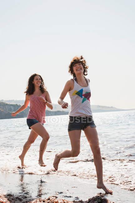 Les femmes courent dans les vagues sur la plage — Photo de stock