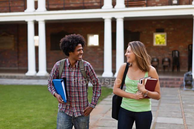 Студенты смеются вместе на кампусе — стоковое фото