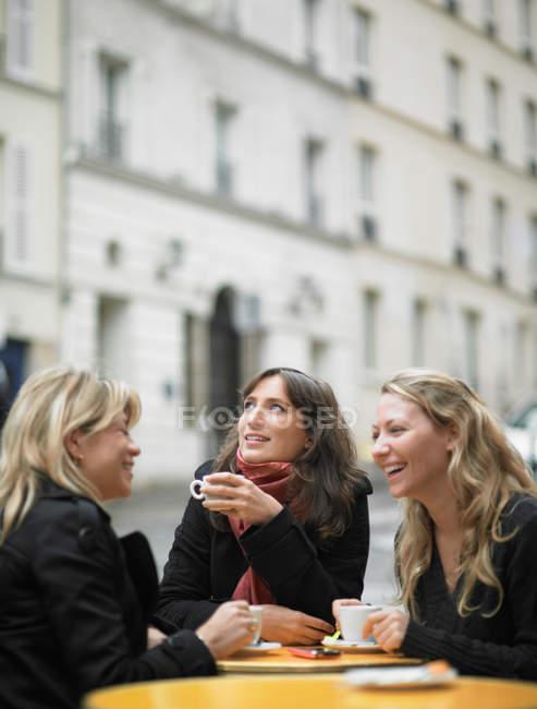 Жінки п'ють каву в тротуарі кафе — стокове фото