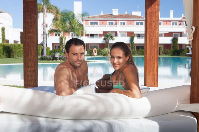 Young couple relaxing on sunlounger at holiday resort — Foto stock
