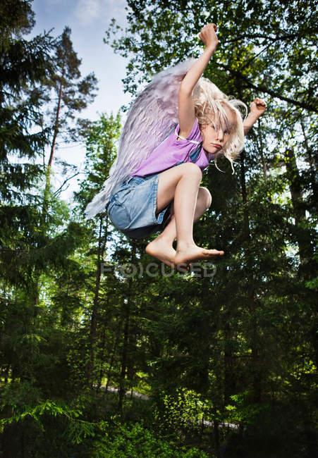 Mädchen tragen Flügel und springen im Wald — Stockfoto