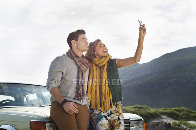 Young couple leaning against car taking selfie on smartphone, Cape Town, Western Cape, South Africa — Stock Photo