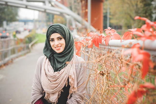 Retrato de una joven apoyada contra una valla en el sendero del parque - foto de stock