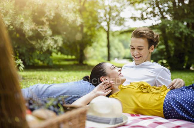 Junges Paar liegt zusammen auf Picknickdecke — Stockfoto