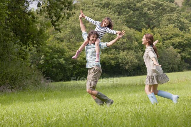 Famiglia che corre in campagna — Foto stock