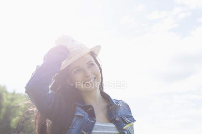 Молодая женщина улыбается, держа шляпу — стоковое фото