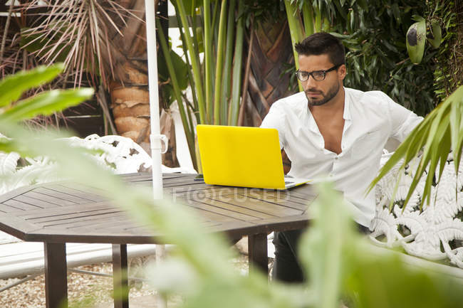 Homem usando laptop no pátio ao ar livre — Fotografia de Stock