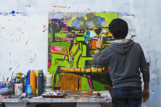 Задній вигляд художника живопис на полотні — стокове фото
