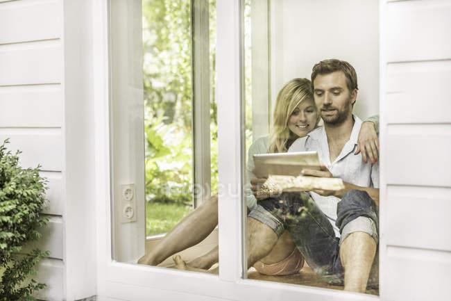 Metà coppia adulta seduta sul pavimento e utilizzando tablet digitale alla finestra della casa — Foto stock