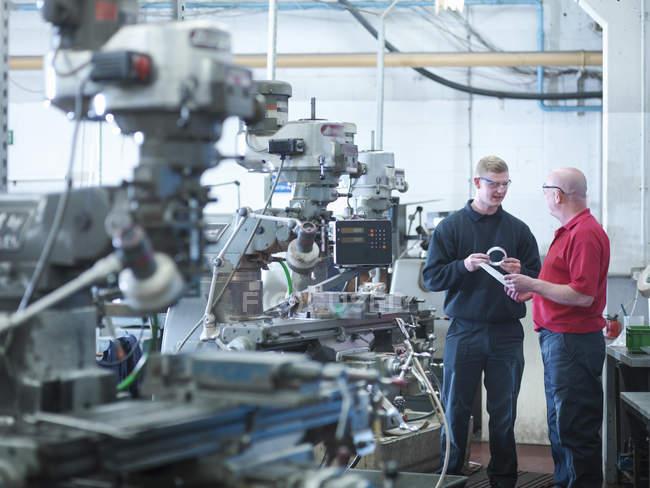 Apprenti ingénieur avec instructeur dans une usine d'ingénierie — Photo de stock