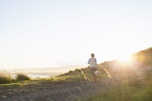 Young woman walking on hill at sunset — Stock Photo