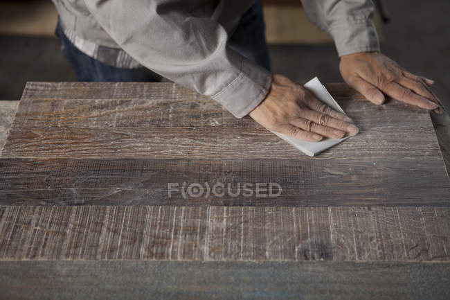 Carpenter smoothing surface of wood plank with sandpaper in factory, Jiangsu, China — Stock Photo