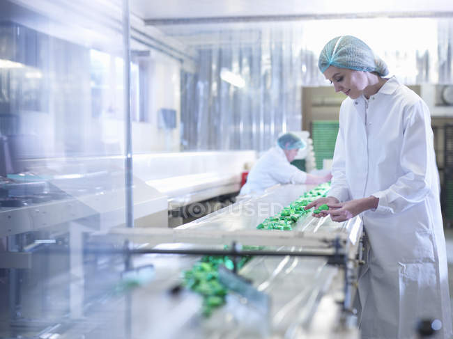 Worker inspecting chocolate on production line in chocolate factory — Stock Photo