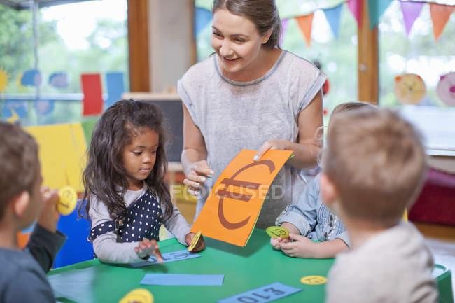 Учитель и ученики подсчитывают валюту евро в детском саду — стоковое фото