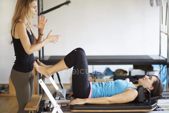 Tutorin weist Studentin in Pilates-Gymnastik auf Reformer ein — Stockfoto
