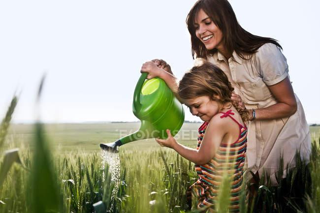 Femme aidant l'enfant avec arrosage peut — Photo de stock