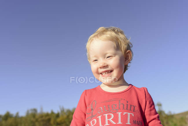 Head and shoulder portrait of cute girl against blue sky — Stock Photo