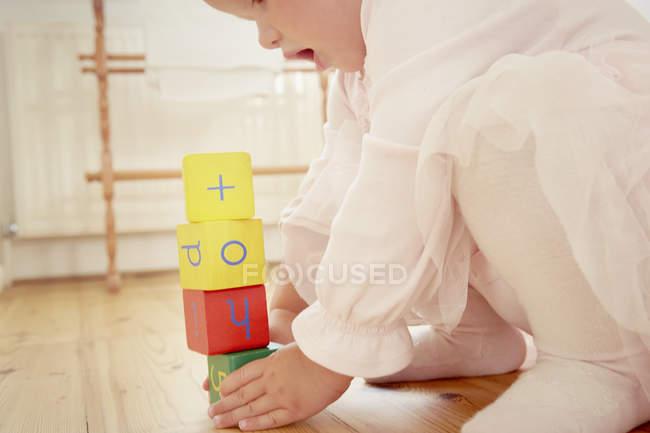 Abgeschnittene Aufnahme von Baby-Mädchen, das Stapel mit Bausteinen baut — Stockfoto