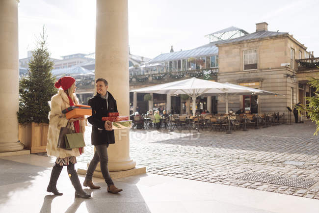 Young couple carrying xmas gifts strolling through Covent Garden, London, UK — Stock Photo