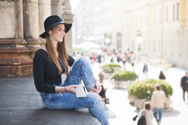 Стильний молодої жінки прослуховування навушників на місто крок — стокове фото