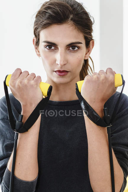 Close up of young woman exercising with resistance bands in living room — Stock Photo