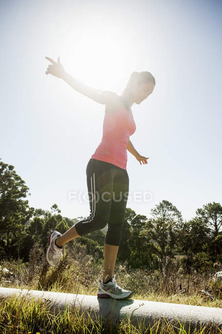 Female jogger balancing on pipe in backlit outdoors — Stock Photo