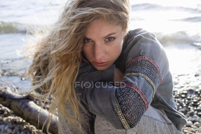 Femme assise sur la plage de vent — Photo de stock