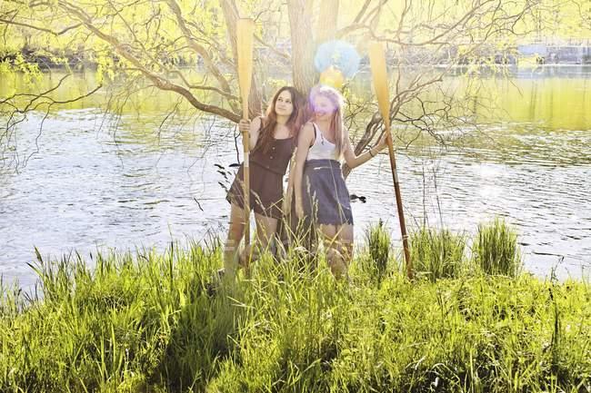Молоді жінки тримають весла водою в підсвічуванням — стокове фото