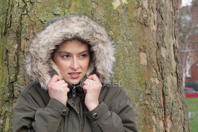 Young woman in front of park tree wrapping up in fur hood — Stock Photo