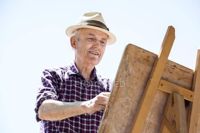 Senior man drawing in park, Hackney, London — Stock Photo