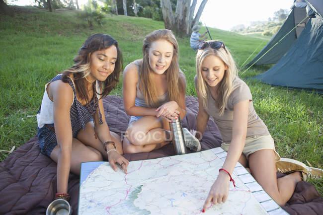Três amigos de fêmeas jovens planejamento roteiam enquanto acampar — Fotografia de Stock