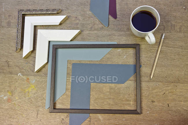 Still life of frames and coffee in picture framers workshop — Stock Photo