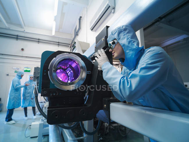 Wissenschaftler in Schutzkleidung und Schutzbrille im Labor neben Lasergeräten — Stockfoto