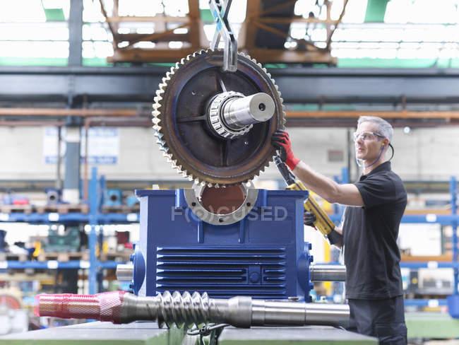 Engineer assembling industrial gearbox in engineering factory — Stock Photo