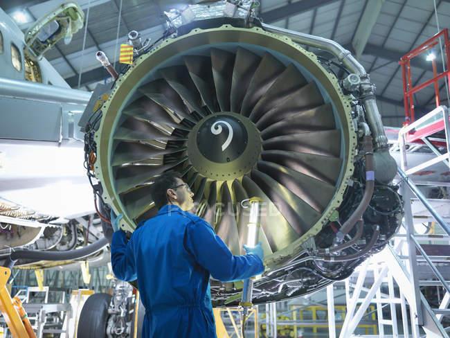 Ingeniero inspeccionando el motor a reacción en fábrica de mantenimiento de aeronaves - foto de stock