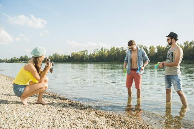Mujer joven fotografiando hombres por lago - foto de stock