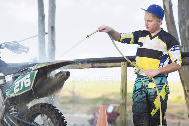 Motociclo giovane concorrente motocross pulizia moto con tubo acqua — Foto stock