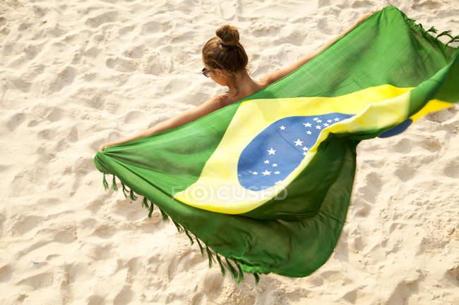 Вид сверху на молодую женщину с бразильским флагом во время танцев, пляж Ипанема, Рио-де-Жанейро, Бразилия — стоковое фото