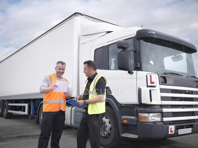 Trainee truck driver receiving pass certificate from instructor — Stock Photo