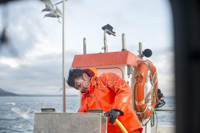 Partial view of Fisherman cleaning fishing boat — Stock Photo