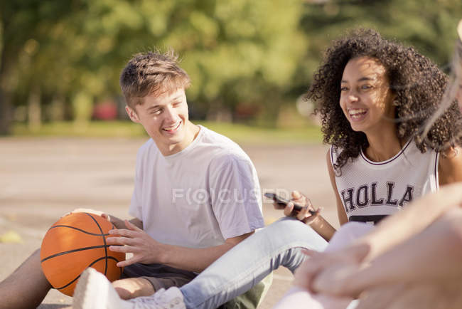 Group of young adult basketball players sitting chatting — Stock Photo