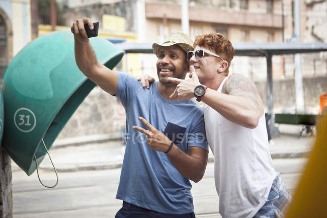 Two male friends taking self portrait using smartphone — Stock Photo