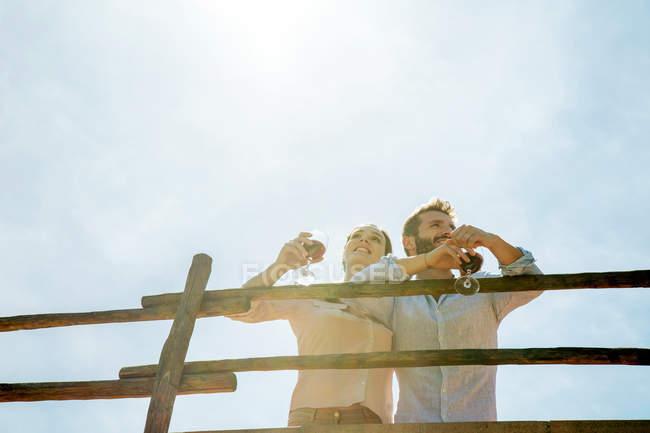 Низький кут зору молода пара проведення чарки фотографіях хтось дивитися вбік — стокове фото