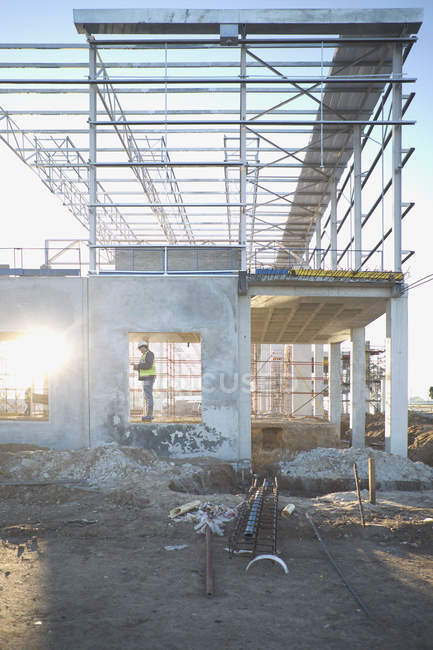 Менеджер участка проверяет оконную раму на строительной площадке — стоковое фото