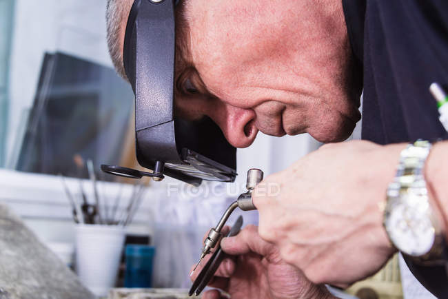Мужній ювелірний майстер за допомогою мініатюрного смолоскипа. — стокове фото