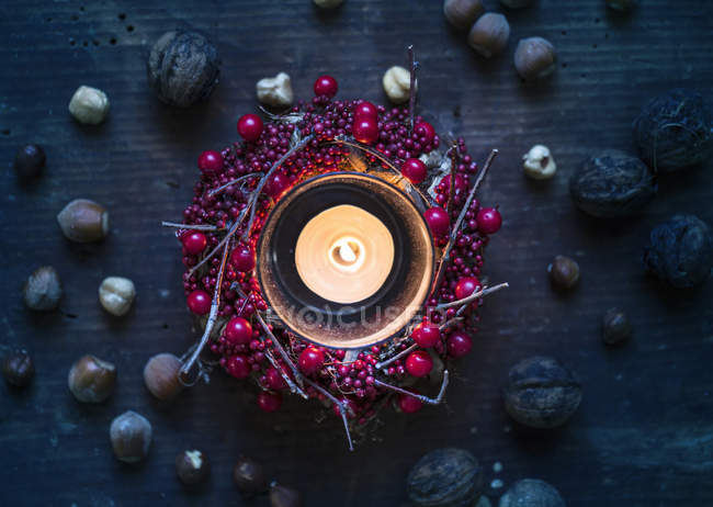 Burning candle surrounded by berry wreath and nuts — Stock Photo