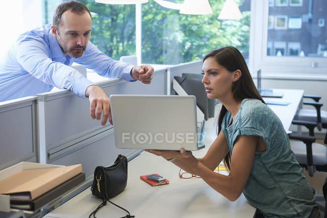 Homme penché sur la partition de l'écran pointant vers l'ordinateur portable — Photo de stock